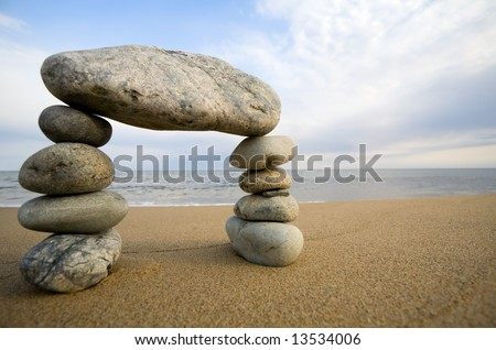 Abstract triumphal arch from a natural stones on a background of the sea - stock photo