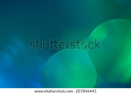 Abstract two big bubbles of water forming a union in front of a blurred background