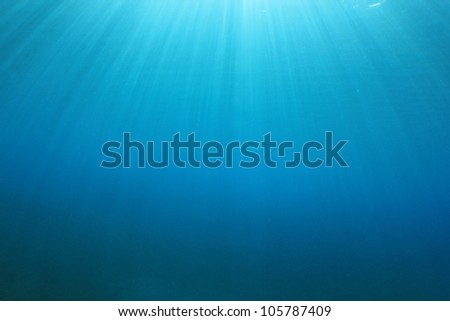 Abstract Underwater Background of Sunbeams in Blue Ocean Water - stock photo