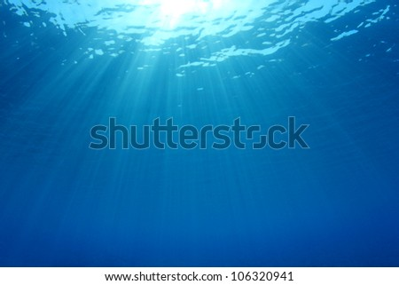 Abstract Underwater Background Photo of Sunbeams in the Blue Ocean - stock photo