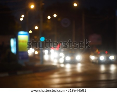 Abstract urban night scene with blurred headlights on the road. Blur and defocused lights on the stream of cars and traffic lights can be used as background. - stock photo