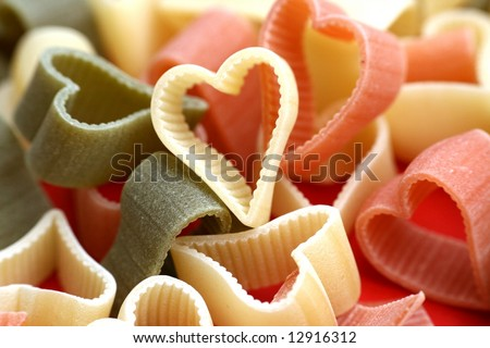 Abstract valentine or food background with uncooked noodles n diffrent colors looks like hearts - stock photo