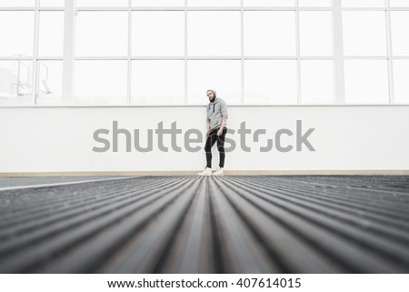 Abstract view from black ground on bearded man standing near window - stock photo