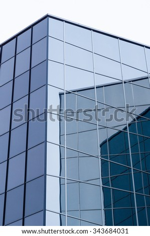 Abstract view of modern glass and steel building with wall reflections