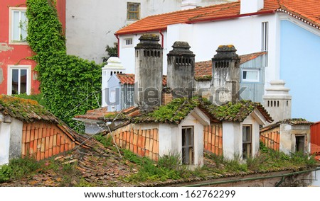 Abstract view of red tiled old decaying rooftops and chimneys in Coimbra, Portugal  - stock photo