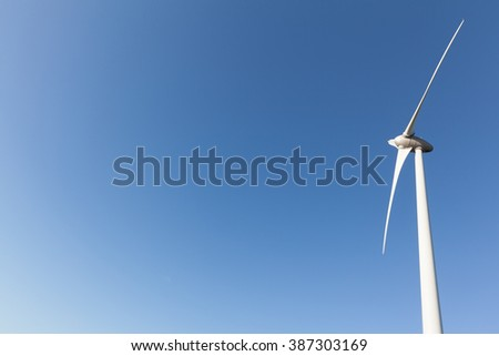 Abstract view of windturbine producing alternative energy with a clear blue sky