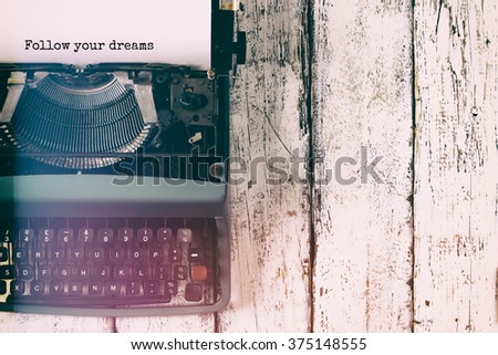 abstract vintage filtered image of top view photo of vintage typewriter with the phrase: follow your dreams, on wooden table. retro filtered image - stock photo