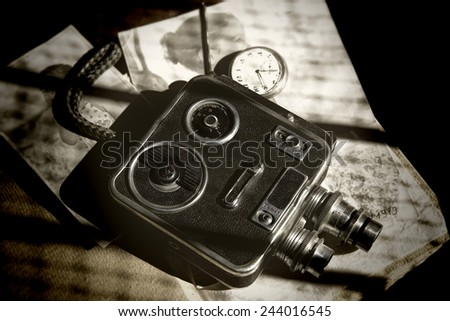 Abstract vintage textured image of an old retro 8mm video camera and photos - stock photo