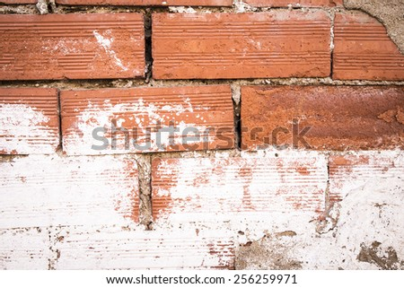 Abstract weathered texture of stained old dark stucco brown and painted red brick wall background in rural room, grungy rusty blocks of stonework technology, colorful horizontal architecture wallpaper - stock photo