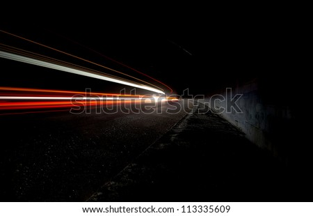 Abstract white and red car lights in a tunnel - stock photo