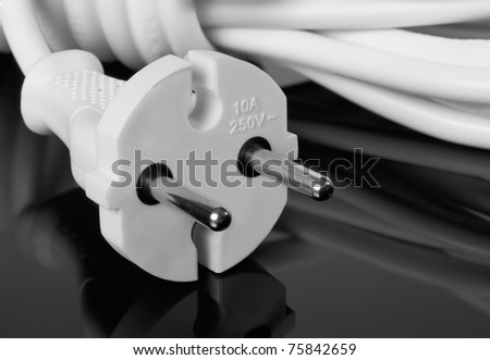 Abstract white europe standard power plug over black background. Copy-space. - stock photo