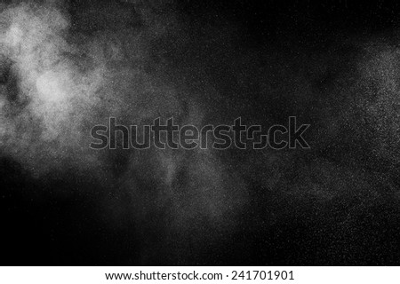 abstract white powder explosion  on black background - stock photo