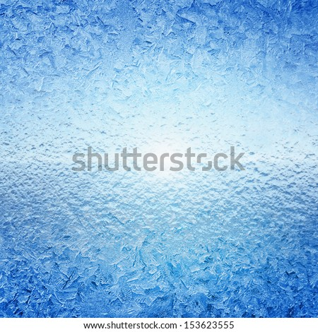 Abstract winter background - frozen water, ice on glass, bright sunlight - stock photo