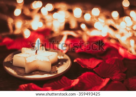 Abstraction. Burning candle in rose petals on the background of lights