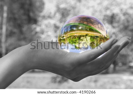 Abstraction. The glass sphere lays on a palm. The turned bright garden with a blossoming tree is visible in sphere. All rest - is decoloured and blur. - stock photo