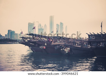 Abu Dhabi buildings skyline with old fishing boats on the front. Filtered shot - stock photo
