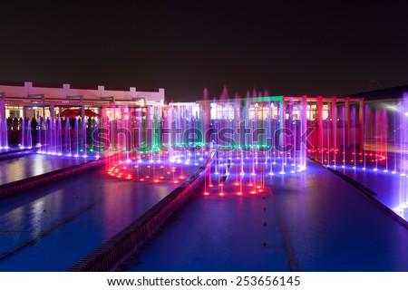 ABU DHABI - DEC 19: Fountain at the Ferrari World Theme Park illuminated at night. December 19, 2014 at the Yas Island in Abu Dhabi, UAE - stock photo