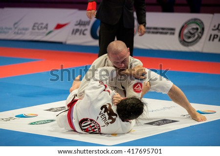 ABU DHABI, UAE - APRIL 19, 2016: ABU DHABI WORLD PROFESSIONAL JIU-JITSU CHAMPIONSHIP 2016 in the IPIC ARENA. Fighters with purple belts fighting in parterre.