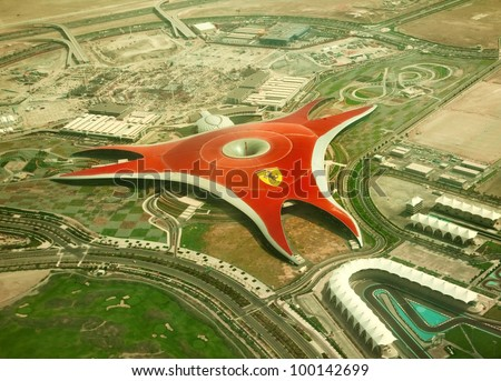 ABU DHABI, UAE -  APRIL 07: Ferrari World Park is the largest indoor amusement park in the world. The roof has a total surface area of 200,000 m2.  Abu Dhabi on April 07, 2012. Bird's eye view - stock photo