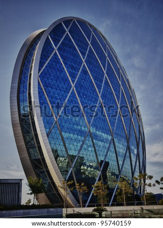 ABU DHABI, UAE - DECEMBER 23 2011: ALDAR HQ tower on 23rd Dec 2011 in Abu Dhabi. It is world's only spherical building.  Aldar HQ has just become the latest landmark of Abu Dhabi. - stock photo