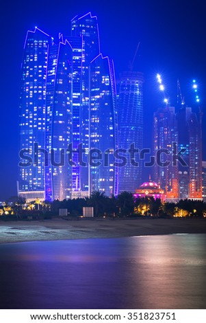 ABU DHABI, UAE - MARCH 28, 2014: Skyscrapers of Abu Dhabi at night with Etihad Towers buildings, UAE. Abu Dhabi is the capital and the second most populous city of the United Arab Emirates - stock photo