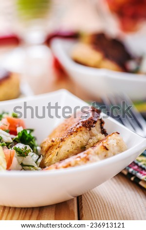 abundance of food on kitchen wooden table on napkin and fork with bowl of salad (radishes, tomatoes, parsley, eggs), meat katlety (pork, beef, lamb) - stock photo
