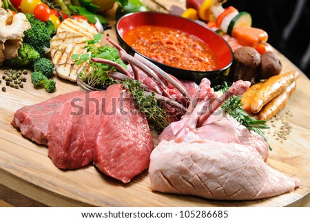 Abundance of raw food on a wooden board - stock photo