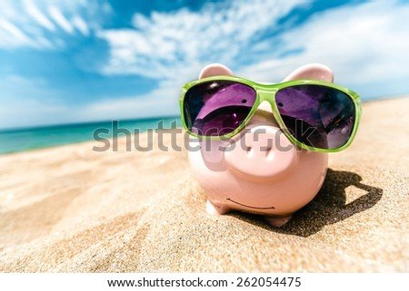 Abundant. Summer piggy bank with sunglasses on the beach - stock photo