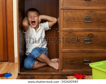 abuse and cruelty to children - little boy is hiding in a cupboard in the room, closing his ears by hands and crying - stock photo