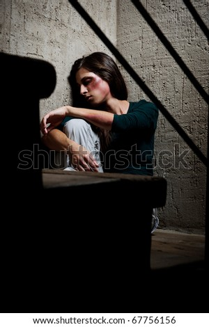 Abused woman in the corner of a stairway comforting herself - stock photo