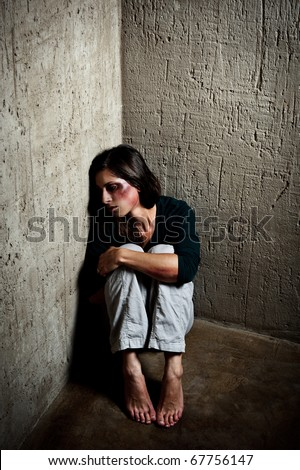 Abused woman in the corner of a stairway comforting herself after getting hit by her husband - stock photo
