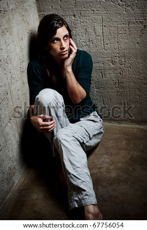 Abused woman in the corner of a stairway touching her face to feel her injuries - stock photo