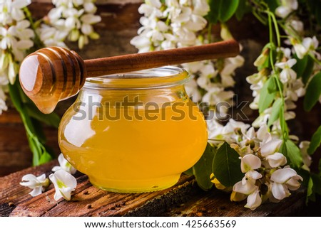 Acacia honey in gar on wooden background. Spring mood. Selective focus. Toned image - stock photo