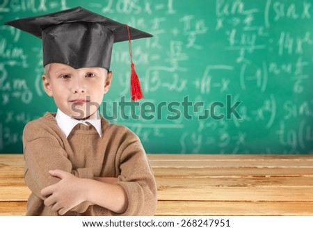 Academic. Portrait of a schoolboy in big round spectacles and academic hat at a classroom. - stock photo