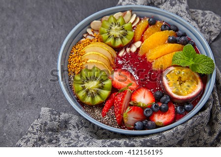 Acai smoothie bowl topped with fruits and berries - stock photo
