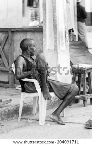 ACCARA, GHANA - MAR 2, 2012: Unidentified Ghanaian man sits on a chair in black and white. People of Ghana suffer of poverty due to the unstable economical situation