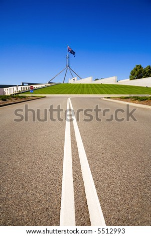 Access road to Parliament House, Canberra, Australia, on a sunny day in January 2006. The Australian flag is flying. The road to power! Copy space. - stock photo