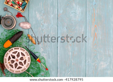 Accessories for fishing on the background of wood. Background of blue color. Reel, fishing line, float, green mesh, hooks a coil of rope, black boots made of rubber. Bait for fishing. - stock photo