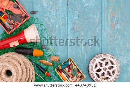 Accessories for fishing on the background of wood. Background of blue color. Reel, fishing line, float, green mesh, hooks, red flashlight, a coil of rope, black boots made of rubber. Bait for fishing. - stock photo