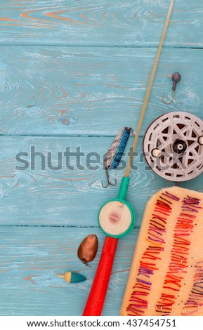 Accessories for fishing on the background of wood. Background of blue color. Several float, hook, sinker, rod for ice fishing. Bait for fishing. - stock photo