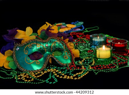 Accessories for Mardi Gras including a mask, beads and lit candles.  Low light evening image with copy space. - stock photo