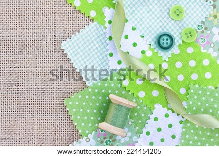 Accessories for needlework: fabric, tape, buttons, coil of threads on canvas - stock photo