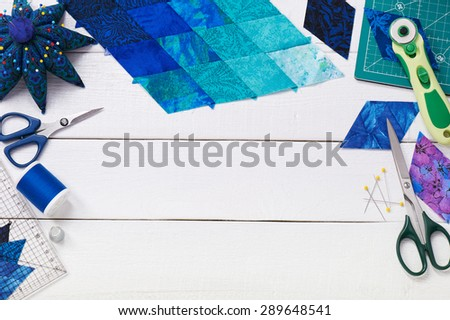 Accessories for patchwork top view on a white wooden surface - stock photo