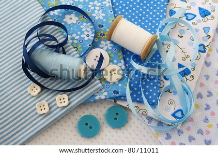 Accessories for sewing: threads, fabric, buttons in blue-white color - stock photo