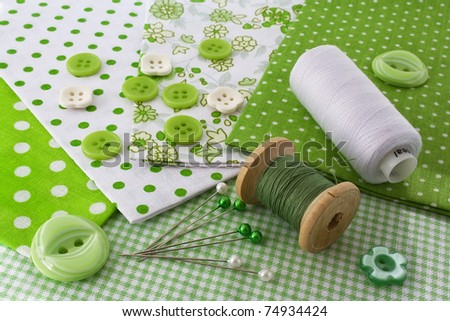 Accessories for sewing: threads, fabric, buttons in green-white color - stock photo