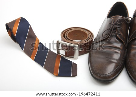 Accessories for the well dressed businessman with a stylish striped tie, brown leather belt and classic brown leather lace-up shoes on a white background - stock photo