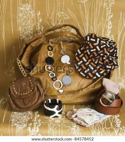 accessories in floral background on a women brown bag - stock photo