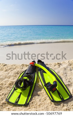 Accessory for Snorkeling -mask, flippers,  tube-lay on sand on background of ocean