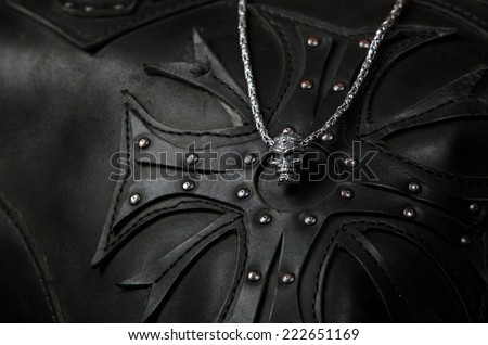 Accessory in the form of a skull on a leather lining in the form of a cross (shallower depth of field) - stock photo
