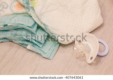 Accessory set for Baby disposable diapers on a turquoise background tree, items for baby care. Lay diaper nappy, the parent taking care of a baby. safe baby ear sticks - stock photo